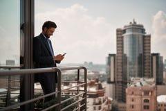 Homem em massagens da leitura do terno do escritório no telefone imagens de stock royalty free