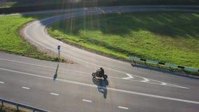 Homem em movimentações da motocicleta com uma estadia do por do sol da junção Tiro de seguimento aéreo do dron 4K filme