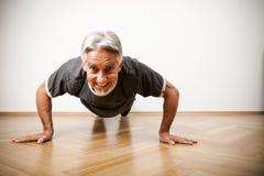 Homem em seu 50s que faz flexões de braço Foto de Stock Royalty Free