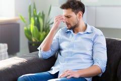 Homem em Sofa Having Headache fotos de stock royalty free