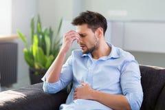 Homem em Sofa Having Headache fotos de stock