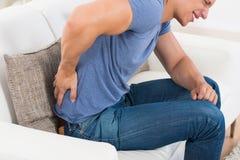 Homem em Sofa Suffering From Backpain imagens de stock royalty free
