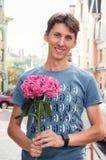 Homem em sorrisos e em olhares do amor na câmera Em suas mãos guarda uma hortênsia cor-de-rosa imagens de stock royalty free