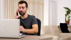 Homem em sua sala de visitas que fala no telefone e que datilografa no computador video estoque