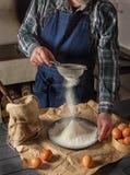 Homem em um avental azul da sarja de Nimes que peneira a farinha Na tabela são os ovos e a farinha fotos de stock royalty free