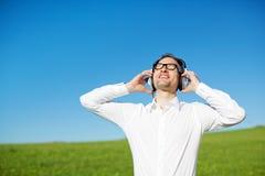 Homem em um campo verde que aprecia sua música Imagens de Stock