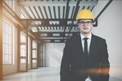 Homem em um capacete em uma sala vazia da fábrica Imagem de Stock Royalty Free
