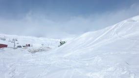 Homem em um carro de neve que salta de um cume do céu azul com nuvens e neve branca fresca vídeos de arquivo
