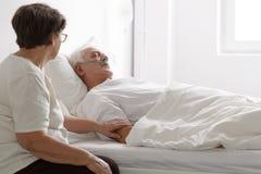 Homem em um coma e sua esposa que senta-se ao lado dele fotografia de stock royalty free