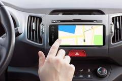 Homem em um dedo do jogo do toque do carro em um mapa da navegação imagem de stock