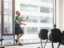 Homem em um gym que joga uma garrafa acima no ar Imagem de Stock Royalty Free