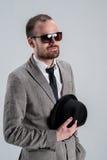 Homem em um homem de negócios do revestimento com vidros em seu HOL da mão Fotografia de Stock Royalty Free