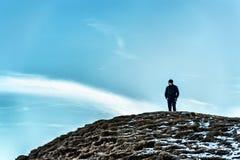 Homem em um monte que olha afastado de pensamento Imagem de Stock Royalty Free