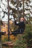 Homem em um parque em um parque da aventura Cidade da corda parque do país para esportes foto de stock royalty free