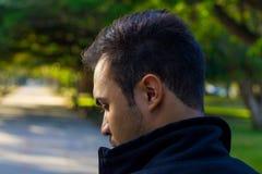 Homem em um parque que olha para trás Imagens de Stock Royalty Free