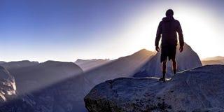 Homem em um penhasco e em umas montanhas majestosas em Yosemite imagem de stock