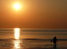 Homem em um por do sol do mar Imagens de Stock Royalty Free