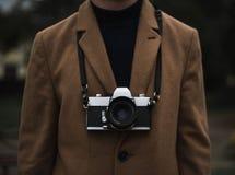 Homem em um revestimento com uma câmera do filme do vintage fotografia de stock royalty free