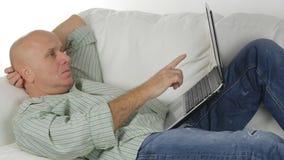 Homem em um sofá que olha preocupado a um portátil que aponta com dedo imagem de stock royalty free