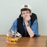 Homem em um tampão uniforme na tabela com navio Fotografia de Stock Royalty Free