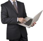 Homem em um terno de negócio escuro que aponta em um portátil Fotografia de Stock Royalty Free