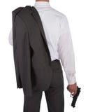 Homem em um terno que guarda uma arma Foto de Stock