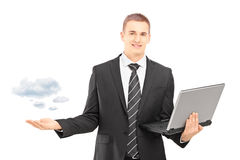 Homem em um terno que guardara um portátil e que gersturing Fotos de Stock