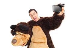 Homem em um traje do urso que toma um selfie Fotografia de Stock Royalty Free