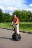 Homem em um 'trotinette'-Segway elétrico Fotos de Stock Royalty Free