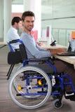Homem em uma cadeira de rodas usando um computador Imagens de Stock Royalty Free