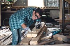 Homem em uma camisa e nas calças de brim de manta que aplanam a plaina manual de madeira na oficina fotografia de stock