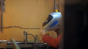 Homem em uma camisa vermelha e em umas condutas vestindo de uma máscara protetora que soldam o trabalho video estoque
