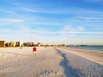 Homem em uma camisa vermelha que toma fotos no Sandy Beach branco de s sob um céu nebuloso com as nuvens macias brancas imagem de stock royalty free