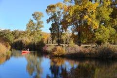 Homem em uma canoa vermelha Fotos de Stock Royalty Free