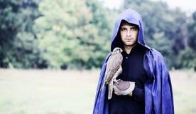 Homem em uma capa de chuva com um falcão Imagem de Stock