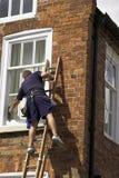 Homem em uma escada Fotos de Stock Royalty Free