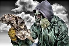 Homem em uma máscara de gás que olha o esqueleto animal Fotografia de Stock