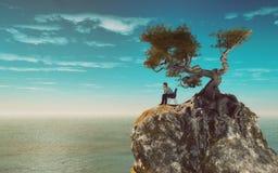 Homem em uma montanha que negligencia o mar Imagens de Stock Royalty Free