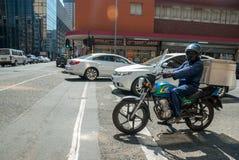 Homem em uma motocicleta da entrega imagem de stock royalty free