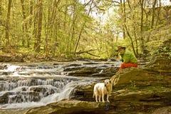 Homem em verde e laranja com cão Fotos de Stock Royalty Free