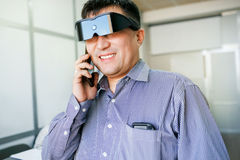 Homem em vidros da realidade virtual que fala no telefone imagem de stock