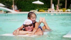 Homem em vidros de sol, em pai e em filha, menina da criança, jogando na água da associação, tendo o divertimento junto Família f filme