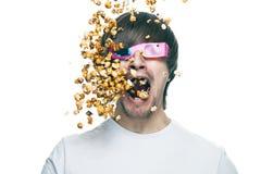 Homem em vidros estereofónicos que come a pipoca Imagens de Stock Royalty Free