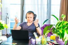 Homem emocional nos fones de ouvido que olham o tela de computador, gestos e participando na reunião em linha, conferência com pa fotos de stock