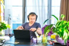 Homem emocional nos fones de ouvido que olham o tela de computador, gestos e participando na reunião em linha, conferência com pa imagem de stock royalty free