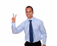 Homem encantador que sorri e que mostra lhe o sinal da vitória Fotos de Stock Royalty Free