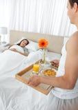 Homem encantador que traz o pequeno almoço a sua esposa Imagem de Stock