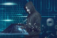 Homem encapuçado com máscara anônima que datilografa no teclado virtual fotografia de stock