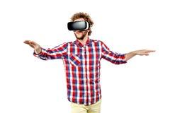 Homem encaracolado-de cabelo novo na camisa de manta usando uns auriculares de VR e um exp fotos de stock royalty free
