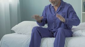 Homem energético que senta-se na cama na manhã que sorri e que estica, aposentadoria feliz video estoque
